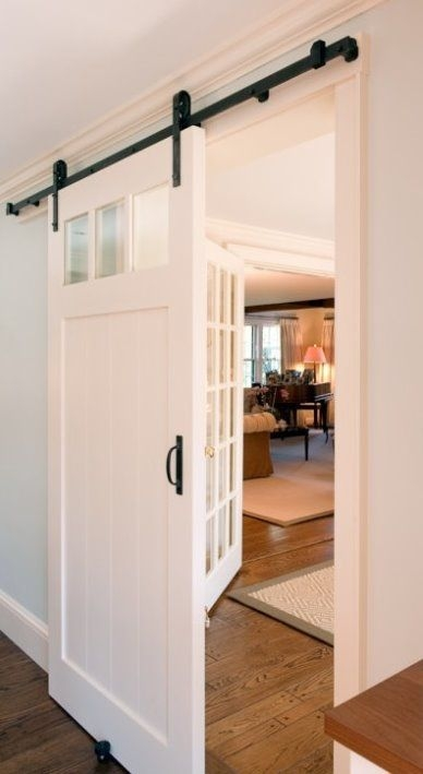 Beautiful white rustic sliding barn door off the foyer to close off the dining room, den, or office area.