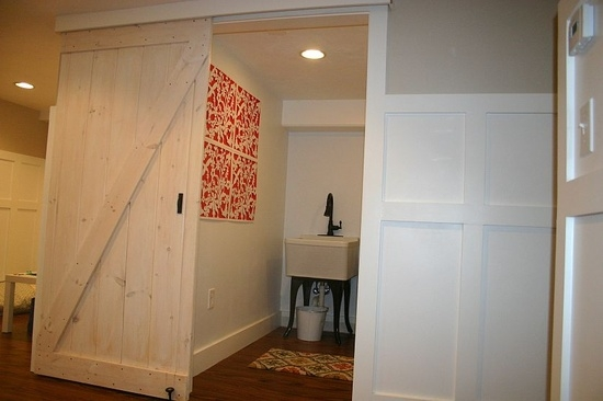 Rustic barn door painted white used as bathroom door in this basement